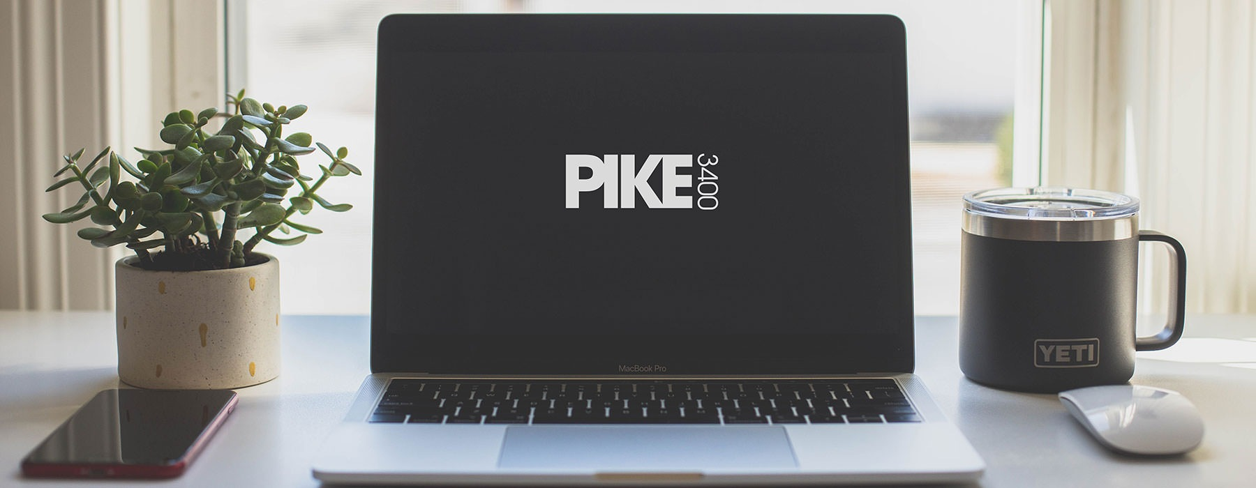 lifestyle image of a laptop displaying the Pike 3400 logo